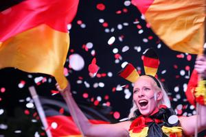 BERLIN, GERMANY - JUNE 09:  A fan celebrates  Germany's 1-0 win over Portugal during the UEFA Champions League soccer match, broadcast from Lviv, Ukraine on a giant outdoor screen near the Brandenburg Gate on June 9, 2012 in Berlin, Germany. The 2012 UEFA European Football Championship, also known as Euro 2012, is a 16-team tournament that Poland is co-hosting with Ukraine.  (Photo by Adam Berry/Getty Images)