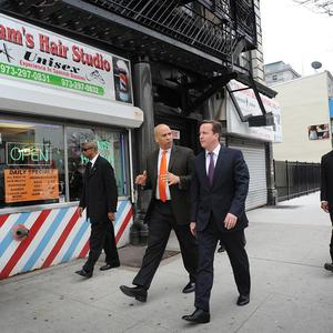 David Cameron walks through the streets of Newark, New Jersey, with Newark Mayor Cory Brooker as his visit to the United States continues