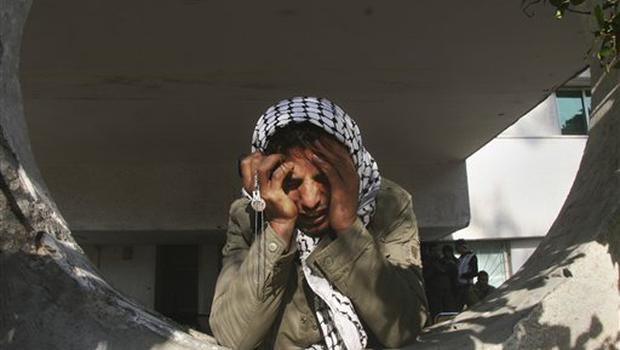 A Palestinian man holds his head in his hands as he reacts at the Shifa Hospital in Gaza City, Monday, Jan. 5, 2009. Israeli forces pounded Gaza Strip houses, mosques and smuggling tunnels on Monday from the air, land and sea, killing at least seven children as they pressed a bruising offensive against Palestinian militants. (AP Photo/Ashraf Amra)