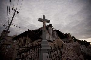 A cross stands intact in front of a church that collapsed during Tuesday's earthquake at the Canape Vert neighborhood