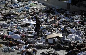 A man looks for a body among hundreds of earthquake victims at the morgue in Port-au-Prince, Thursday, Jan. 14, 2010.