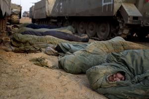 Israeli soldiers sleep next to their armored personal carriers in a staging area near the Israel Gaza Strip Border, southern Israel, Monday, Nov. 19, 2012. The Palestinian civilian death toll mounted Monday as Israeli aircraft struck densely populated areas in the Gaza Strip in a campaign to quell militant rocket fire menacing nearly half of Israel's population. (AP Photo/Ariel Schalit)