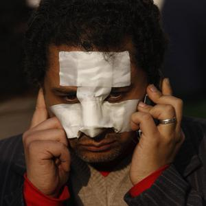 A man with a bandaged face uses a cellular phone during a demonstration in Cairo (AP)