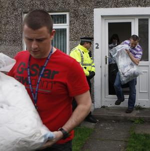 Police carry evidence from a house in Balloch where a suspect arrested in connection with the murder of Pc Ronan Kerr is believed to have lived