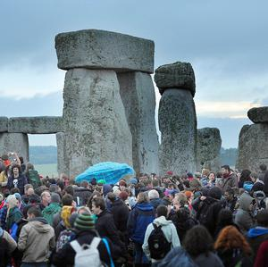 Revellers watch the sunrise of the Summer Solstice at Stonehenge, Wiltshire