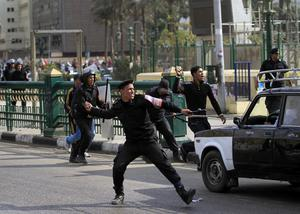 An Egyptian police officer throws a rock at protesters in Tahrir Square in Cairo, Egypt, Saturday, Nov. 19, 2011. Egyptian riot police beat protesters and dismantled a small tent city set up to commemorate revolutionary martyrs in Cairo's Tahrir Square on Saturday. (AP Photo/Khalil Hamra)