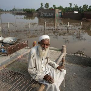 Pakistani Mir Zaman sits on a bed next to his flooded house in Camp Karoona, Pakistan