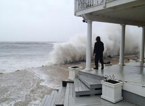 MONTAUK, NY - OCTOBER 29:  A wave crashes against the shore while person stands on a porch as Hurricane Sandy moves up the coast October 29, 2012 in Montauk, New York. Sandy, which has already claimed over 50 lives in the Caribbean, is predicted to bring heavy winds and floodwaters to the mid-Atlantic region.  (Photo by Sheila Rooney/Getty Images) *** BESTPIX ***