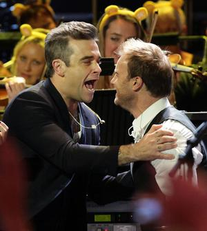 Robbie Williams, left, and Take That's Gary Barlow as Robbie joins his ex-band mates on stage for a special performance