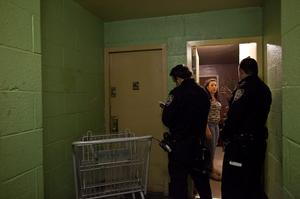 NEW YORK, NY - OCTOBER 28: New York City police officers speak with a woman as they go door to door in a housing project to take note of which residents are ignoring the mandatory evacuation order as Hurricane Sandy approaches on October 28, 2012 in the Rockaway Beach neighborhood of the Queens borough of New York City. New York City Mayor Michael Bloomberg announced a mandatory evacuation on low-lying coastal areas of the city.  Sandy, which has already claimed over 50 lives in the Caribbean is predicted to bring heavy winds and floodwaters to the mid-Atlantic region. (Photo by Allison Joyce/Getty Images)