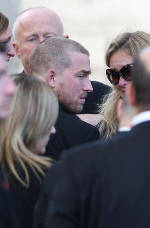 Andrew Cowles is comforted by friends as he attends the funeral of Boyzone singer Stephen Gately at St Laurence O'Toole Church in Dublin