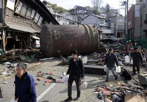 People walk to receive water supply through a street with the rubble Monday March 14, 2011 in Kesennuma, Miyagi Prefecture, northern Japan  following Friday's massive earthquake and the ensuing tsunami. (AP Photo/Kyodo News) JAPAN OUT, MANDATORY CREDIT, NO SALES IN CHINA, HONG  KONG, JAPAN, SOUTH KOREA AND FRANCE