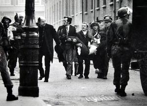 Fr Daly waving a bloody handkerchief as he and several others carry the fatally wounded Jackie Duddy, 17,  past British soldiers on January 30, 1972, known as Bloody Sunday. Picture by Stanley Matchett