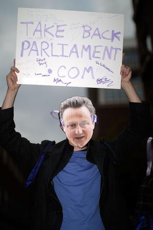 An electoral reform protester wears a mask depecting David Cameron as they gather outside the Workers Foundation in Westminster on May 10, 2010 in London, England