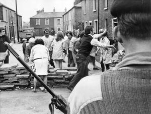 Many hands make light work of removing a barricade at Lemom Street, in the Falls Road area of Belfast as a coldier stands guard.