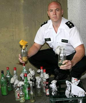 PSNI Inspector John Burrows with the cache of petrol bombs recovered in Derry