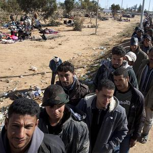 Egyptian refugees wait for food after crossing the Libya-Tunisia (AP)