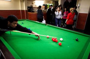 ASHDOD, ISRAEL- NOVEMBER 19:  (ISRAEL OUT)  A Israeli man plays pool as others stand in a billiard room used as a shelter while air raid sirens sound November 19, 2012 in Ashdod, Israel. According to reports November 19, 2012, at least 90 Palestinians have been killed and more than 700 wounded during the Israeli offensive in the Gaza Strip.   (Photo by Lior Mizrahi/Getty Images)