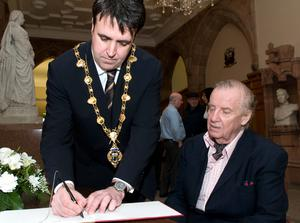 Mayor of Derry is the first to sign the Peace Book in the city's Guildhall, followed by longtime civil rights campaigner Ivan Cooper. The book was opened to the public following the vigil that was held in Guildhall Square