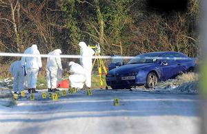 Forensic officers examine the scene of the car bomb explosion on the Milltown Road in Antrim yesterday