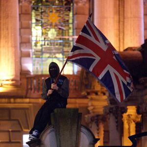 A Loyalist flag protester on the wall of Belfast City Hall, a month after the city council decided to fly the Union Flag on designated days only