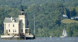 Tents are seen at Astor Courts in Rhinebeck, N.Y., right, as a sail boat moves along the Hudson River past the Rondout Lighthouse in Port Ewen, N.Y., on Saturday, July 31, 2010.