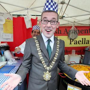 Belfast's lord mayor Niall O Donnghaile lends a hand at a paella stand on his first engagement at the spring continental market at City Hall