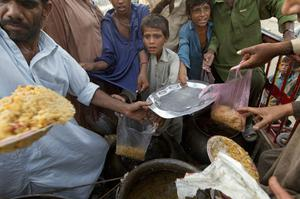Desperate flood victims scramble during a food distribution by a local Muslim organization offering rice for the hungry survivors over two weeks after the floods started