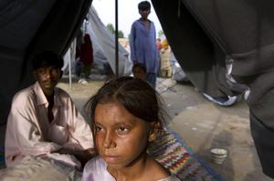 A Pakistani girl sits in a tented camp where some families have taken shelter after their homes were flooded