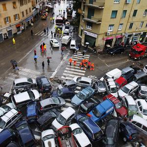 Cars swept into a pile by Friday's torrential rains on a street in Genoa (AP)