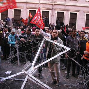 Protesters move barbed wire set up by Egyptian military near Tahrir Square in Cairo (AP)