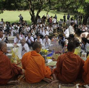 Victims pray in front of Buddhist monks during a ceremony near the site of the Khmer Rouge's former 'killing fields' (AP)