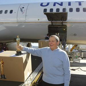 Tom Sherak poses with an Oscar statue after landing at Los Angeles International Airport (AP/Chris Carlson)