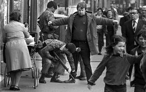 April 1984 Man is searched by the British Army on Belfast's Falls Road as people go about their businness, hardly seeming to register that this was happening. Picture by Brendan Murphy