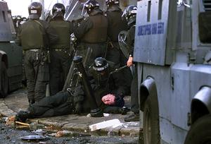 July 2001 An RUC man lies injured during a riot in Ardoyne before an Orange parade returns passed a Nationalist area on the 12th July 2001. Picture by Ann McManus