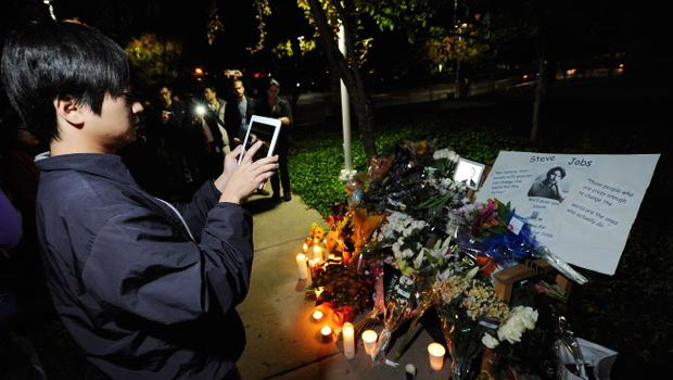CUPERTINO, CA - OCTOBER 05:  A crowd gathers at a makeshift memorial for Steve Jobs at the Apple headquarters on October 5, 2011 in Cupertino, California. Jobs, 56, passed away after a long battle with pancreatic cancer. Jobs co-founded Apple in 1976 and is credited, along with Steve Wozniak, with marketing the world's first personal computer in addition to the popular iPod, iPhone and iPad.  (Photo by Kevork Djansezian/Getty Images)