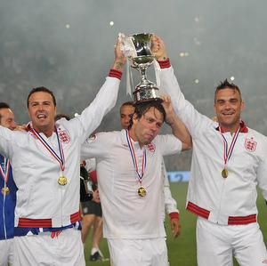 Paddy McGuiness, left, John Bishop, centre, and Robbie Williams celebrate England's victory in the Soccer Aid match