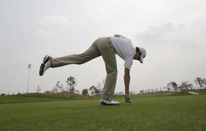 Rory McIlroy sets the ball for teeing off from the 1st tee during the Pro-Am tournament of the Masters golf tournament in Shanghai, China on Wednesday Oct. 24, 2012. (AP Photo/Eugene Hoshiko)