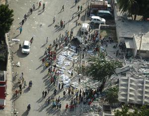 Aerial photo provided by The American Red Cross shows survivors gathered around bodies in Haiti's capital Port-au-Prince during a joint Red Cross Red Crescent/ECHO (European Community Humanitarian Organization) aerial assessment mission following Tuesday's devestating earthquake.