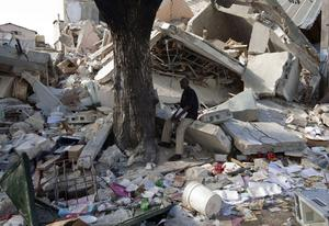 A man sits among the rubble of collapsed buildings in Port-au-Prince, Thursday, Jan. 14, 2010