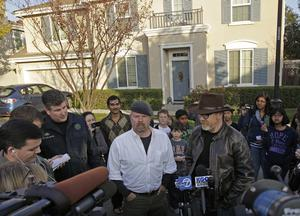 """""""Mythbusters"""" stars Adam Savage, right, and Jamie Hyneman speak to the media outside the home damaged by an errant cannonball fired during a filming of an episode of their show, Wednesday, Dec. 7, 2011"""