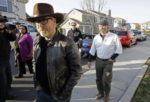 """""""Mythbusters"""" stars Adam Savage, left, and Jamie Hyneman approach the home damaged by an errant cannonball fired during a filming of an episode of their show, Wednesday, Dec. 7, 2011 in Dublin, Calif."""
