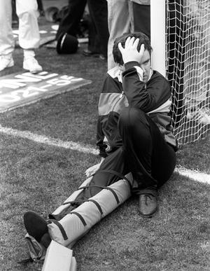 An injured fan sits against the goalpost with his leg in a splint