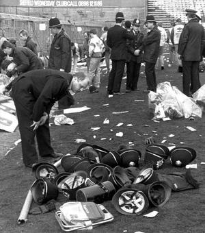 Hillsborough disaster policeman looks at a pile of police helmets lying on pitch amongst debris