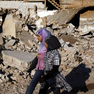 Syrian girls walk near to the rubble of a house which was destroyed in the town of Taftanaz (AP)