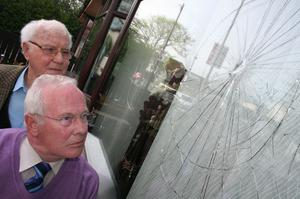 Frank McAuley and Len Kane examine the broken window at his houseby