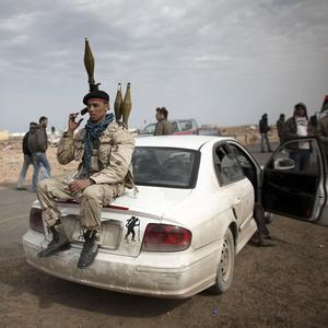 A volunteer in Libya's rebel group sits on the back of a car on the outskirts of the eastern town of Ras Lanouf (AP)