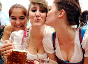 Women in traditional dress pose with beer mugs at the Oktoberfest beer festival