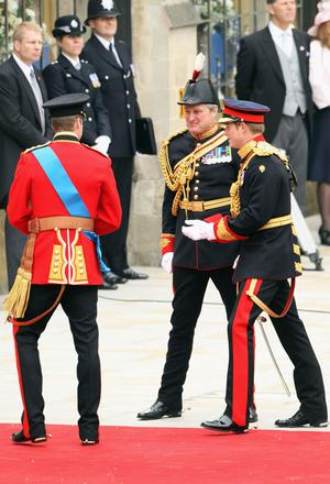 LONDON, ENGLAND - APRIL 29:  An officer (C) speaks to Prince William (L) as he arrives with Prince Harry (R) for the Royal Wedding of Prince William to Catherine Middleton at Westminster Abbey on April 29, 2011 in London, England. The marriage of the second in line to the British throne is to be led by the Archbishop of Canterbury and will be attended by 1900 guests, including foreign Royal family members and heads of state. Thousands of well-wishers from around the world have also flocked to London to witness the spectacle and pageantry of the Royal Wedding.  (Photo by Dan Kitwood/Getty Images)