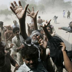 Pakistan flood survivors jostle for position as a military helicopter delivers relief goods (AP)